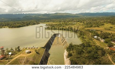 Aerial View Dam On The Lake In The Rainforest On The Island. Water Flowing From The Dam, Water For I