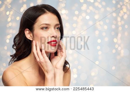 beauty, make up and people concept - happy smiling young woman with red lipstick over holidays lights background touching her face