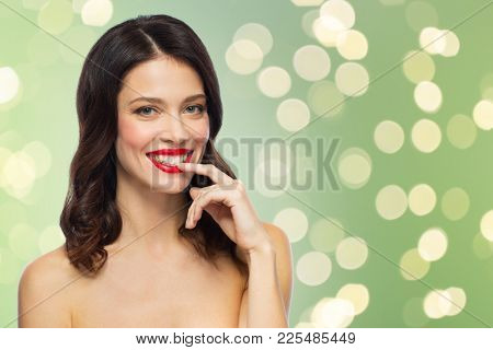 beauty, make up and people concept - happy smiling young woman with red lipstick posing over green background with lights