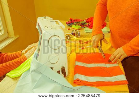 Fashion Designer, Woman Tailor Posing At Her Workplace With Cut Fabric, Free Space On Wooden Wall. T