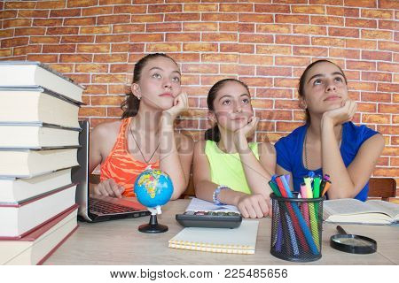 Three Teenager Girl Doing Homework At The Table At Home. Education And School Concept. Young Girl St