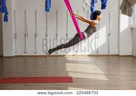 Adult Woman Practices Inversion Anti-gravity Yoga Position In Gym. Aerial Antigravity Yoga Girl On P
