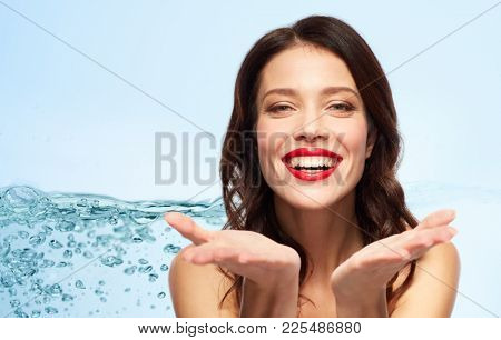 beauty, make up and people concept - happy smiling young woman with red lipstick holding something imaginary on palms over blue background with bubbles in water splash