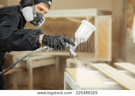 Man In Respirator Mask Painting Wooden Planks At Workshop. Male Applicate Paints And Varnishes. Pneu