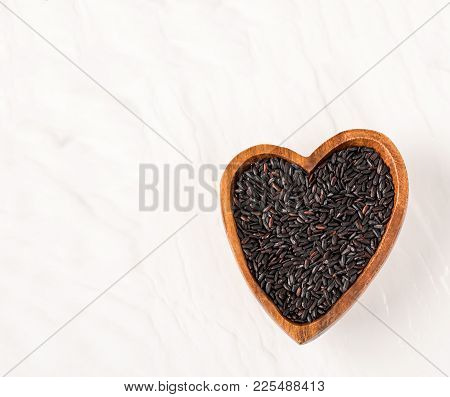 Isolated Handful Of Raw Black, Nero Rice In The Wood Bowl In The Shape Of Heart On White Background