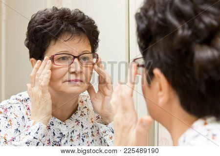 Senior Woman Trying On New Glasses And Looking At Herself In The Mirror