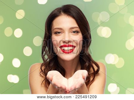 beauty, make up and people concept - happy smiling young woman with red lipstick holding something imaginary on palms over green background with lights