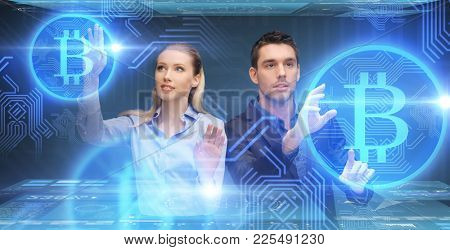 business, cryptocurrency, finance and technology concept - businessman and businesswoman with virtual bitcoins