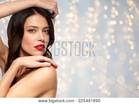 beauty, make up and people concept - close up of happy smiling young woman with red lipstick posing over holidays lights background