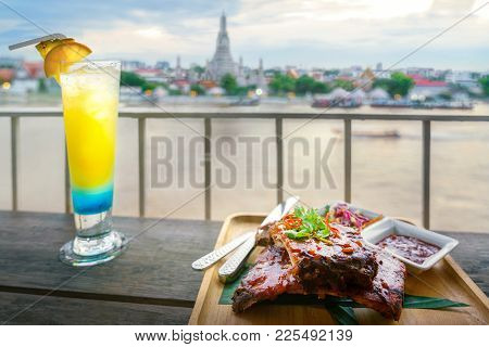 Rib Stake And Mocktail Juice In Dinner Table With Arun Temple Background On Restaurant In Bangkok, T