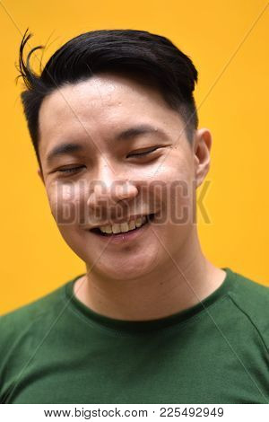A Young Asian Male Chinese Smiling With Eyes Shut