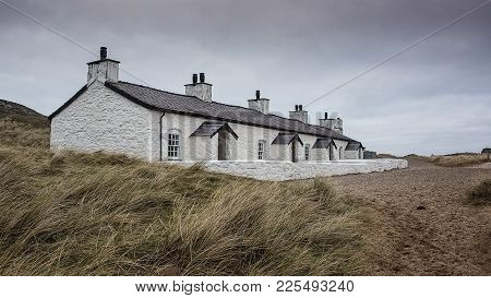 A Photograph Of A Row Of Old Fishermans Cottages On The Beach In Bleak Weather