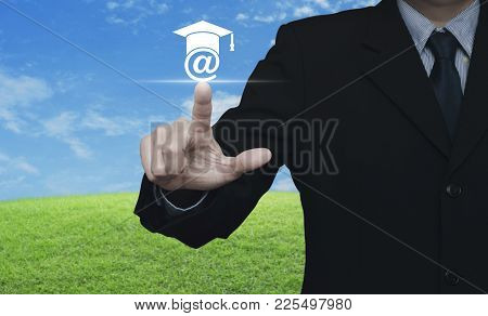 Businessman Pressing E-learning Icon Over Green Grass Field With Blue Sky, Study Online Concept