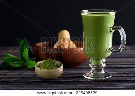 Matcha Green Tea Latte Beverage In Glass Cup On Dark Wooden Background