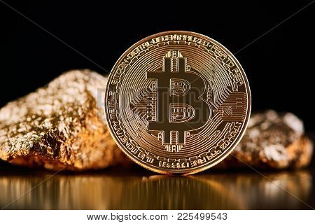 Golden Bitcoin In Front Of Gold Lumps Representing Futuristic World Trends Both Isolated On Black Ba