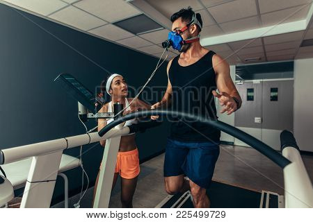 Woman Giving Instruction To Male Runner On Treadmill In Laboratory. Runner With Mask On Treadmill In