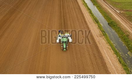 Aerial View Special Tractor Equipped With Equipment For Planting Green Vegetables And Lettuce In The