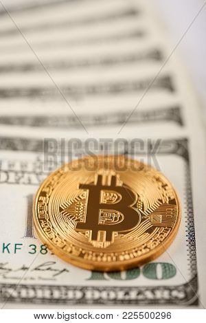 Golden Bitcoin On Top Of Stack Of Hundred Dollar Banknotes Representing Future Trend Of Virtual Mone