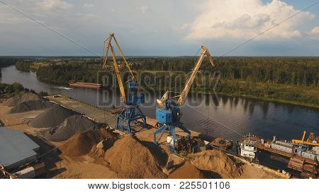 Aerial:port Cargo Cranes And Ship Fragment At The Docks.aerial View:container Cranes In Cargo Port T
