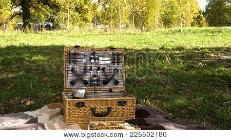 Wooden Basket For Picnic With Plates. Basket For A Picnic In The Park On A Sunny Day. Outdoor Picnic