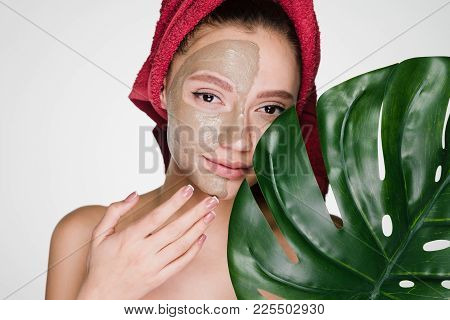 A Surprised Woman With A Towel On Her Head Apply A Cleansing Mask And Poses In The Camera