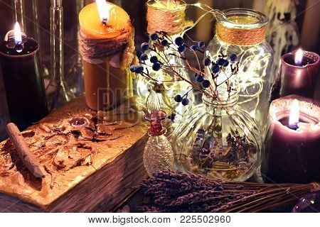 Evil Book With Black Candles, Glass Bottles, And Herbs On Witch Table. Occult, Esoteric, Divination