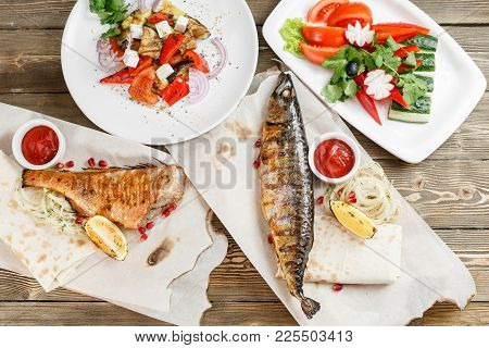 Grilled Mackerel And Sea Bass. Salad Of Fresh Vegetables. Serving On A Wooden Board On A Rustic Tabl