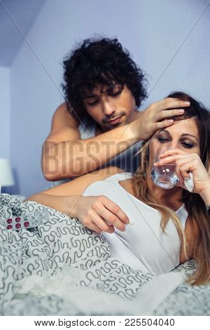 Sick Woman Drinking Water After Take Medicines While Young Man Holding Her Head With Hand Palm. Sick