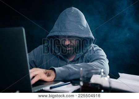 A Male Hacker Is Sitting In A Dark Room And Something Is Typing On A Laptop
