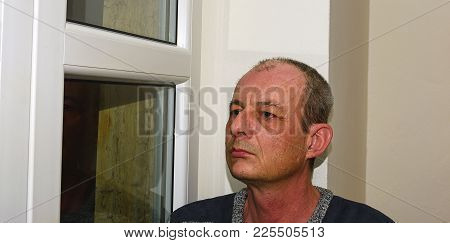 Depressed Middle Age Man Sitting Near Window.