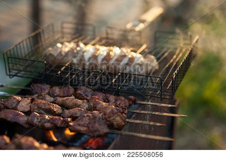 Shish Kebab On The Grill. Marinated Shashlik Preparing On A Barbecue Grill Over Charcoal.