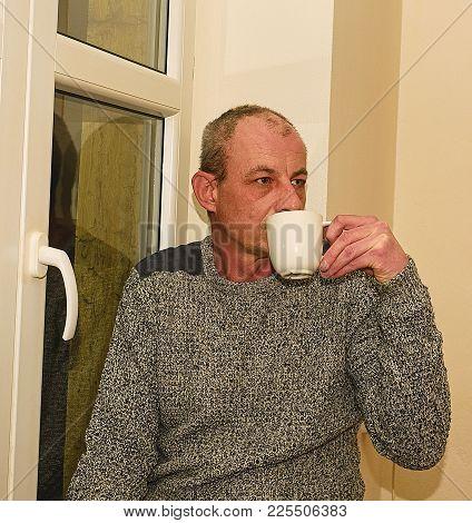 Depressed Middle Age Man Sitting Near Window. Sad Man Drinking Coffee.