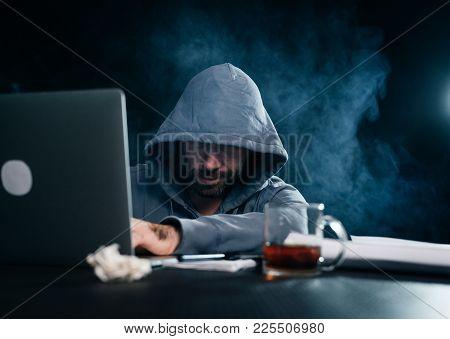 Male Hacker In A Sweatshirt With A Hood Sitting In A Dark Room