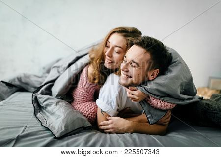 Couple In Love Having Fun In Bed And Smiling. A Couple In Love Having Fun In The Bed. Copy Space. So