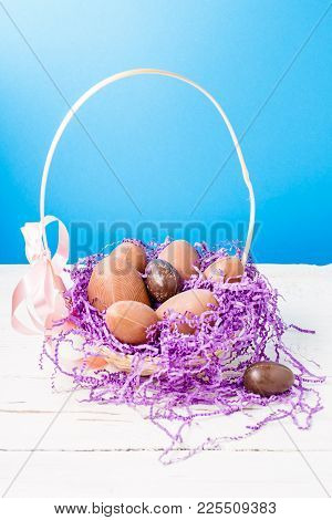 Image Of Chicken, Chocolate Eggs, Purple Decorative Paper In Basket On Empty Blue Background