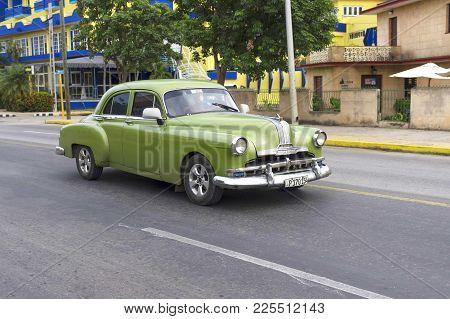 Varadero, Cuba-01.01.2018: Vintage Classic American Car Rides Down The Street  Varadero With People
