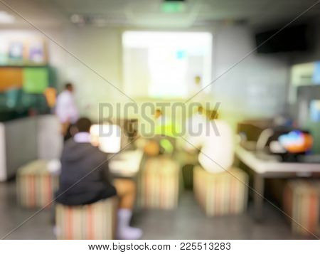 Blurred Image Of Students Are Learning And Sitting At Desk Using Computer Lap Together And Lecture I