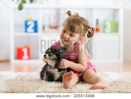 Kd Girl And Her Dog Play In Nursery