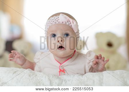 Portrait Of A Cute Young Baby Girl Wearing A Bodysuit Shirt Lying On Belly In Nursery Room