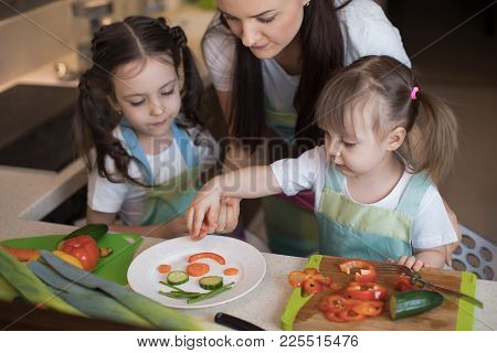 Happy Family Mother And Kids Daughter Are Preparing Healthy Food, They Improvise Together In The Kit