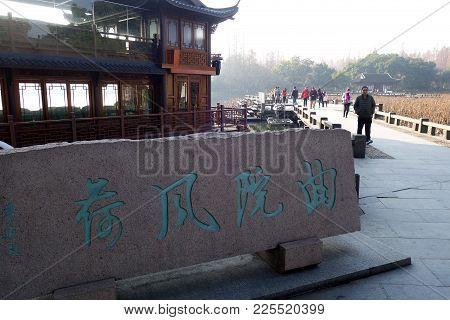 Tourists Cross A Bridge At Hangzhou's West Lake
