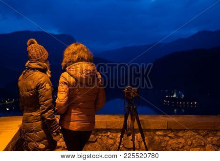 two female friends visiting castle Bled at night and taking pictures of the lake with the famous illuminated pilgrimage church of the Assumption of Blessed Mary and island, Slovenia