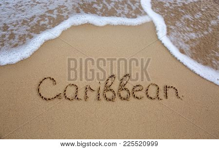 Word Caribbean Written On The Sand Near The Sea. Travel Background.
