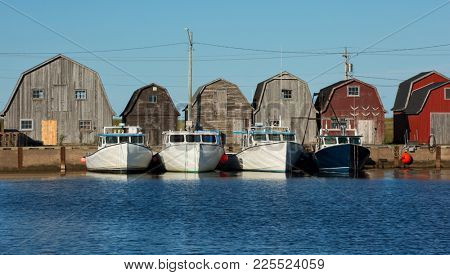 Blue fishing boat in front of oysters barns in Malpeque, Prince Edward island also called PEI