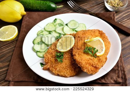Tasty Schnitzel With Cucumber Salad On White Plate. Close Up View