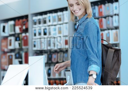 High Spirited. Amazing Blonde Bowing Head And Smiling While Choosing New Device For Herself