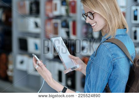 Show Your Mood. High Spirited Girl Standing In Semi Position And Bowing Head While Using Smartphone