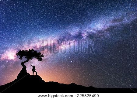 Space With Milky Way. Silhouette Of A Woman With Backpack At Night. Girl On The Mountain Peak And St