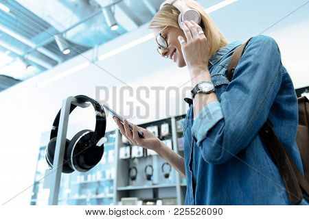 Listening Song. Enigmatical Young Woman Expressing Positivity And Touching Headphones While Looking