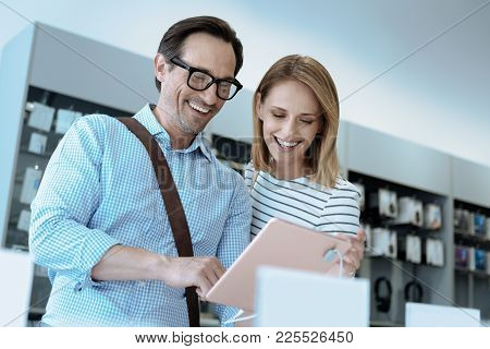 Stay Positive. Delighted Male Person Keeping Smile On His Face And Bowing Head While Testing New Dev
